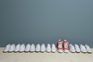 A red pair on Converse stands out in a line of plain white shoes