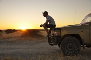 Sunset with a man sitting on the front bumper of a jeep